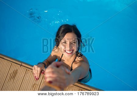 View From Above Of Girl With Snow-white Smile In The Swimming Pool Holding A Man's Hand Trying To Ge