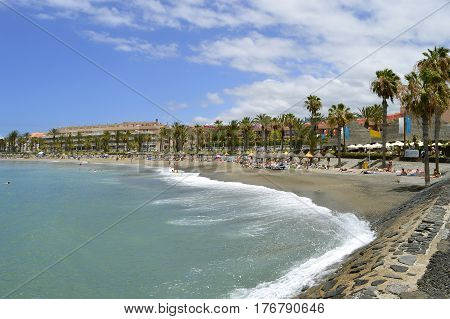 Playa De Las Americas beach Tenerife Canary Islands Spain Europe - June 18 2016: Tourists on the beach enjoying the sun
