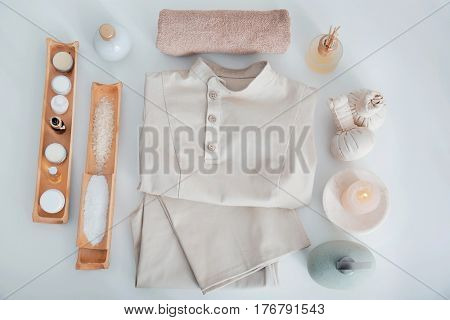 Spa uniform and supplies of masseur on light background