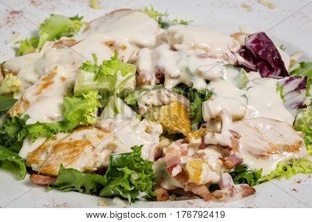 Ensalada de bacon con salsa cesar y trozos de pan frito