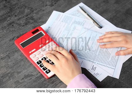 Female hands with calculator and individual income tax return form, closeup