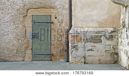 An old door with antique hinges and door handle in an old wall with a copper rain downpipe at the side.