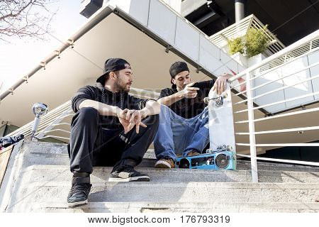 Two Young Skateboarder Relax On The Outskirts Stairs