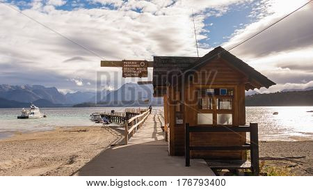 Patagonian wooden pier / In a lake, with mountains in the horizon and the sun coming from the side