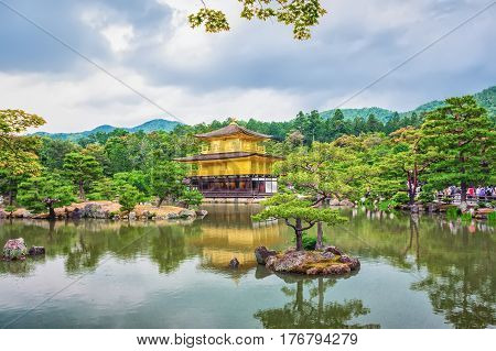 KYOTO JAPAN - MAY 29 2016 : Golden Pavilion Temple in Kyoto Japan against gloomy cloudy sky