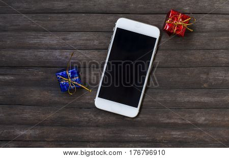 White smartphone with gifts on rustic wooden table. Black screen smartphone on shabby chic background. Presents and phone with blank text place. Personal device and colorful gifts flat lay composition