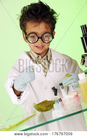 A tiny young mad scientist in a lab coat, gloves and coke-bottle glasses, attempting to grasp gooey green slime.  He works on a glass table with test tubes, bottles and a microscope.