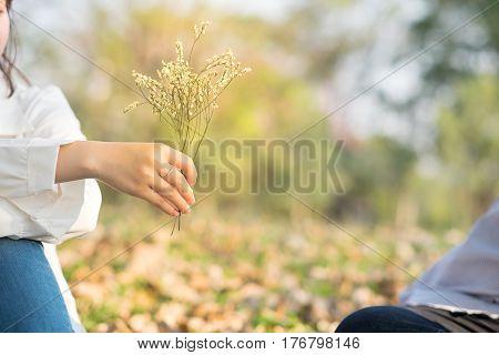 Young Woman Sending Flower For Boyfriend In Public Garden