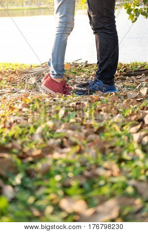 girlfriend hold hand boyfriend and her making height for kiss him in public garden have small lake background