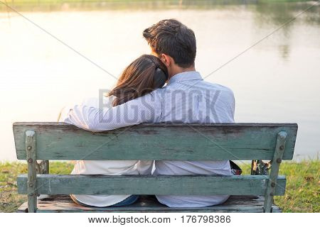 girlfriend and boyfriend sitting on bench and being hugging in public garden have small lake background