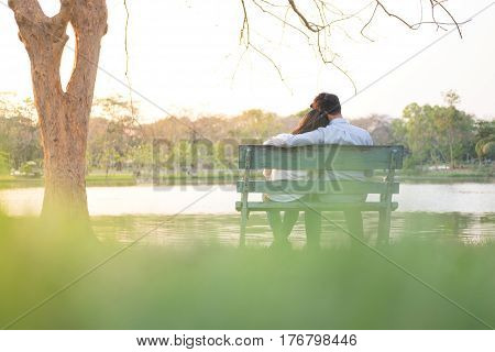 Girlfriend And Boyfriend Sitting On Bench And Being Hugging In Public Garden Have Lake Background