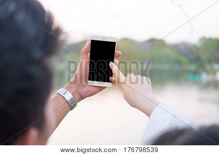 Young Woman And Boyfriend Being Using Smartphone For Selfie In Public Garden Sunset Time Have Lake B
