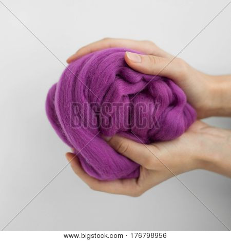 Close-up of violet merino wool ball in hands.