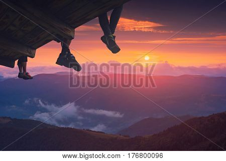 Hikers sit on a wooden flooring above the mountain valley and enjoy sunset.