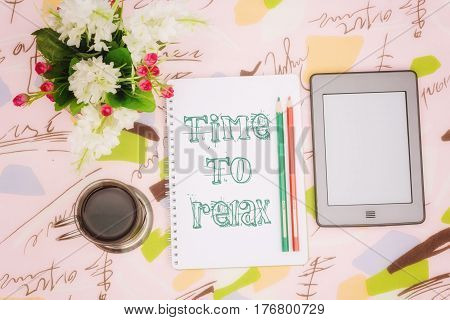Coffee cup, notebook and ebook with an inscription: time to relax