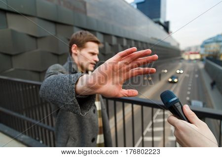 A young man is categorically against giving an interview to a journalist on the street
