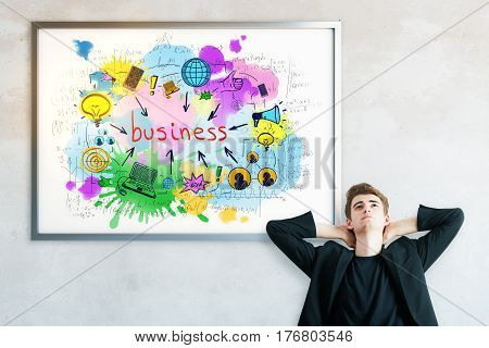 Relaxing european man on concrete background with business sketch in frame. Trade concept