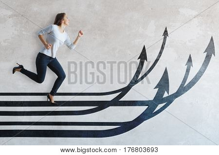 Side view of young caucasian girl running on drawn upward arrows on light concrete background. Growth concept