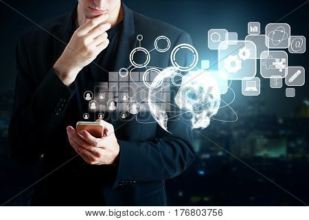 Male hands using smartphone with digital business charts icons and globe. Blurry night city background. Technology concept. 3D Rendering