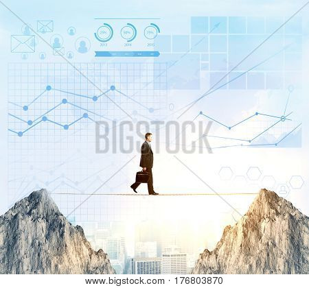 Side view of businessman walking on rope between two cliffs on city background with digital business charts. Risk concept