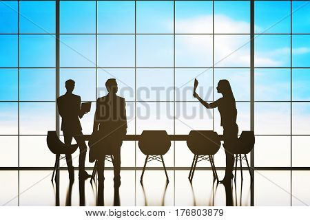 Backlit businessmen and women silhouettes having meeting in conference room with panoramic blue sky view. Communication concept