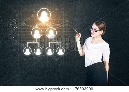 Smiling young businesswoman pointing at staff pyramid on concrete background. Leadership concept
