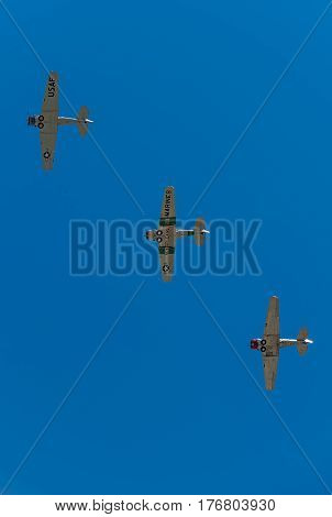 EDEN PRAIRIE MN - JULY 16 2016: Three AT6 Texan airplanes fly in formation against clear sky at air show. The AT-6 Texan was primarily used as trainer aircraft during and after World War II.