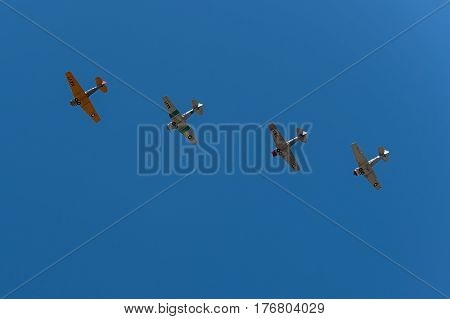 EDEN PRAIRIE MN - JULY 16 2016: Four AT6 Texan airplanes fly in formation against clear sky at air show. The AT-6 Texan was primarily used as trainer aircraft during and after World War II.