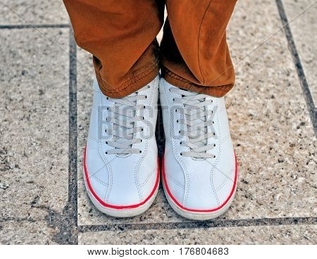 Top view of child's white casual shoes and trousers