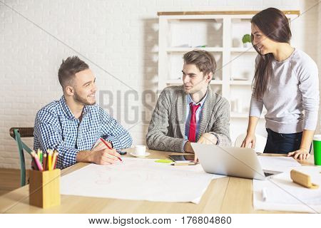 Happy young people in modern office working on project together while sitting at wooden desk with various items. Teamwork concept