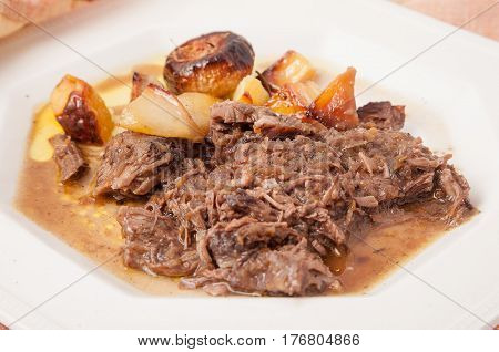 Elegant set of braised potatoes and onions in a white English ceramic dish and indian tablecloth.
