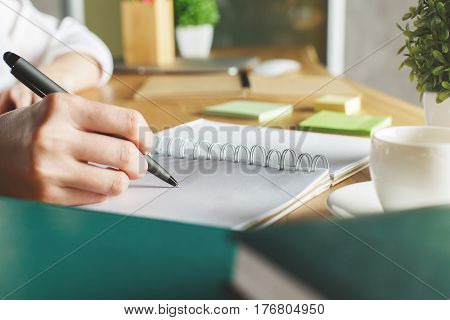 Side view of girl's hand writing in spiral notepad placed on wooden desktop with coffee cup and decorative plant