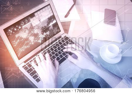 Top view of female hands using laptop with business charts on screen. Trading concept. Filtered image