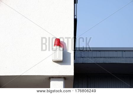 A red warning light with a speaker throws a shadow on a white wall.