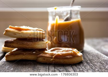 biscuits with salted caramel and sesame. caramel pot wooden background. cookies heart
