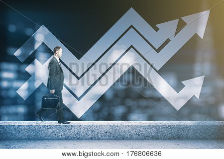 Side view of businessman walking on the edge of concrete rooftop with panoramic blurry night city view and upward arrows. Success and finance concept