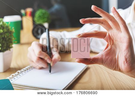 Girl writing in empty spiral notepad placed on wooden desktop with items and holding small pink sticker. Mock up