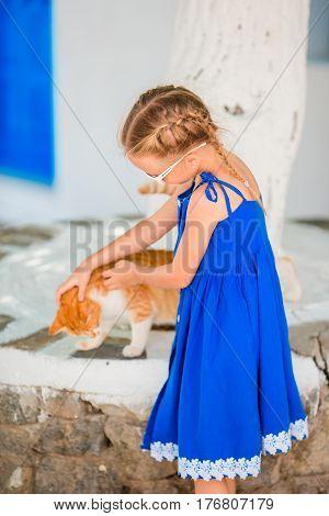 Closeup of Little adorable girl playing a cat in greek village, Mykonos, Greece