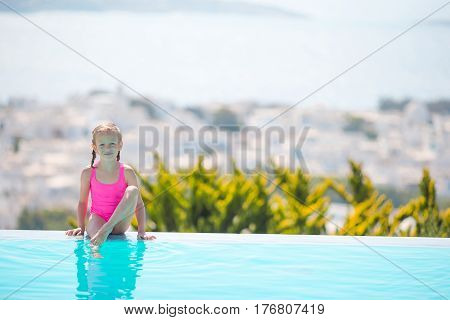 Cute toddler girl standing in shallow water at exotic beach