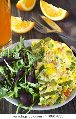 Breakfast scrambled eggs with vegetables and fresh mixed salad