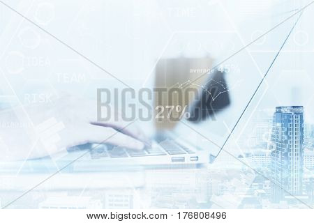 Side view of businessman's hands using laptop with business charts on city background. Double epxosure. Financial growth concept. Filtered image