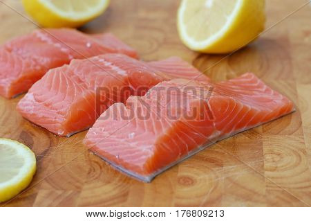 Raw Salmon Fillet With Yellow Lemon On Brown Wooden Background