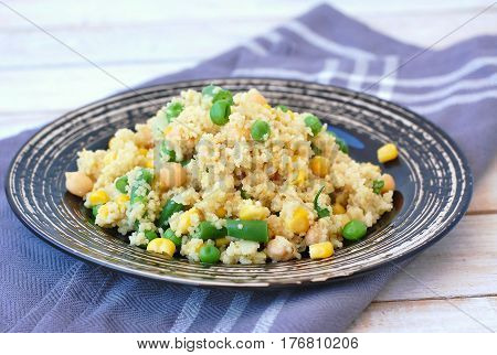 Healthy Vegan Meal With Whole Grain Couscous, Chickpeas, Sweet Corn, Peas, Green Beans On Dark Plate