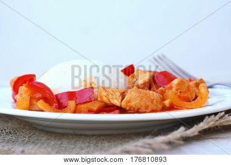 Meal From Chicken Meat With Indian Spices, Green And Red Pepper And Rice On White Plate, Gunny Cloth