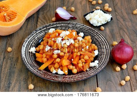 Healthy Meal From Chickpeas, Pumpkin, Red Onion And Cheese On White Plate On Dark Wooden Background