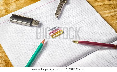 Office supplies on paper necessary for office flash drive for storing information notebook for writing compasses for drawers pencil and pen for writing paper clips for stapling documents