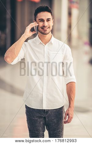 Handsome guy is talking on the mobile phone and smiling while walking down the mall