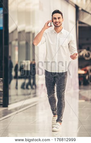 Full length portrait of handsome guy talking on the mobile phone and smiling while walking down the mall