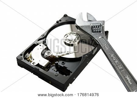 Disassembled Hard Disk without top cover. adjustable wrench on HDD. Computer hardware.