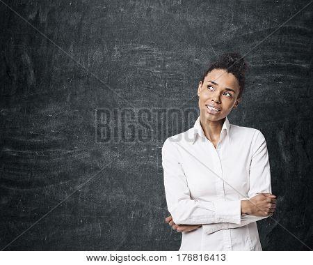 Portrait of a smiling African American businesswoman standing near an empty blackboard. Mock up